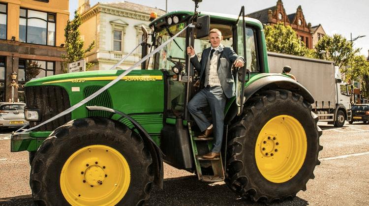 Man in a fancy suit on a John Deere tractor