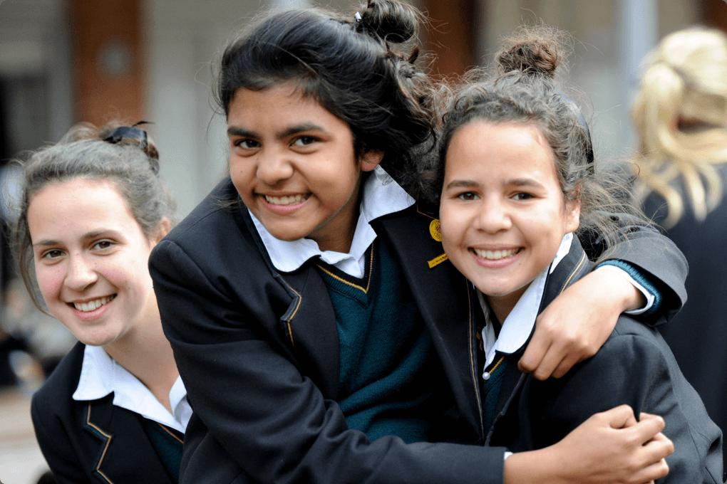 Three smiling girls in school uniforms