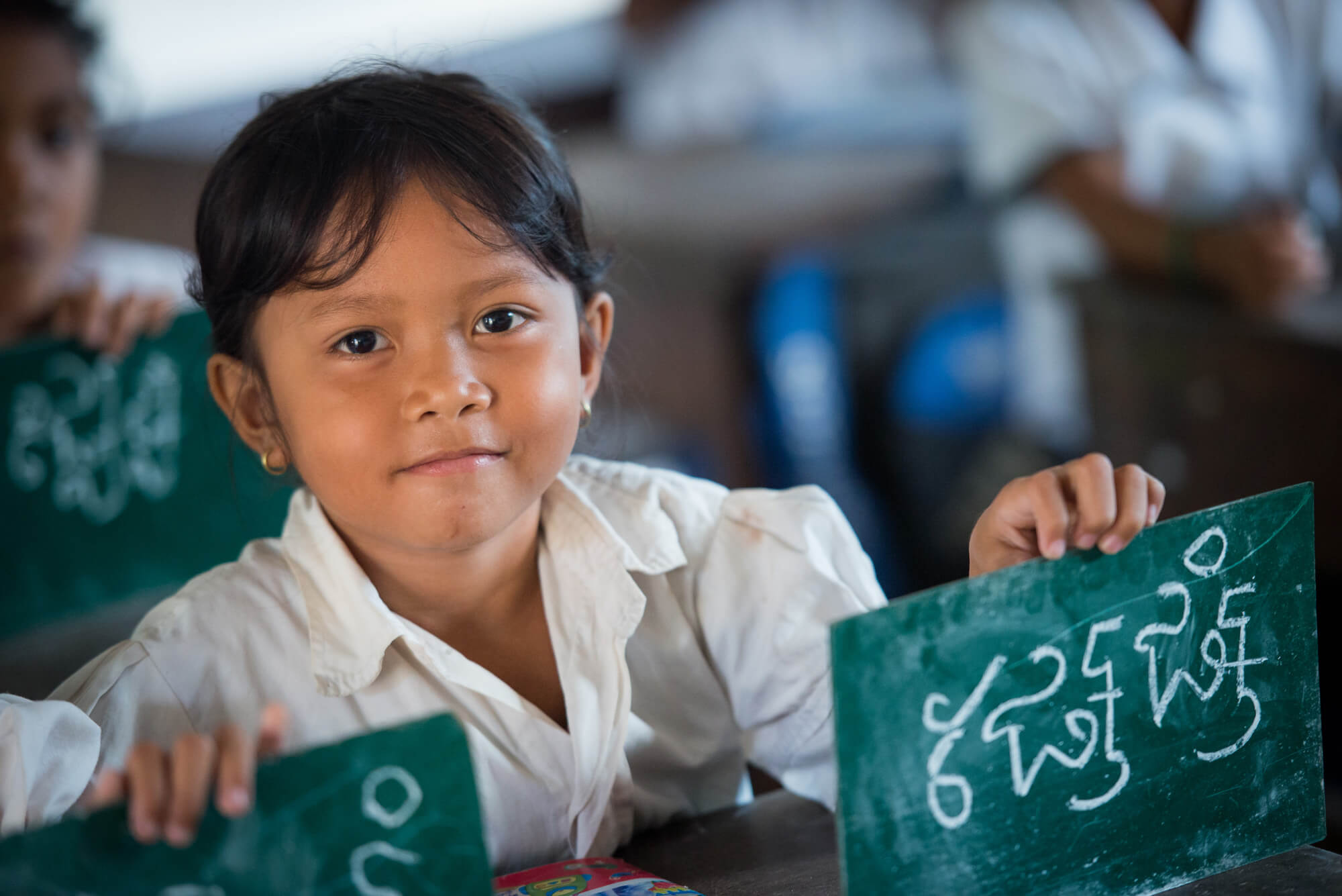 Young child holding up her answer board in classroom