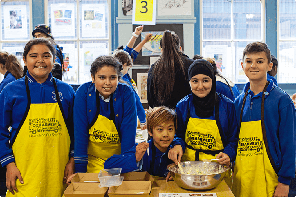 Kids smiling whilst cooking in ozHarvest
