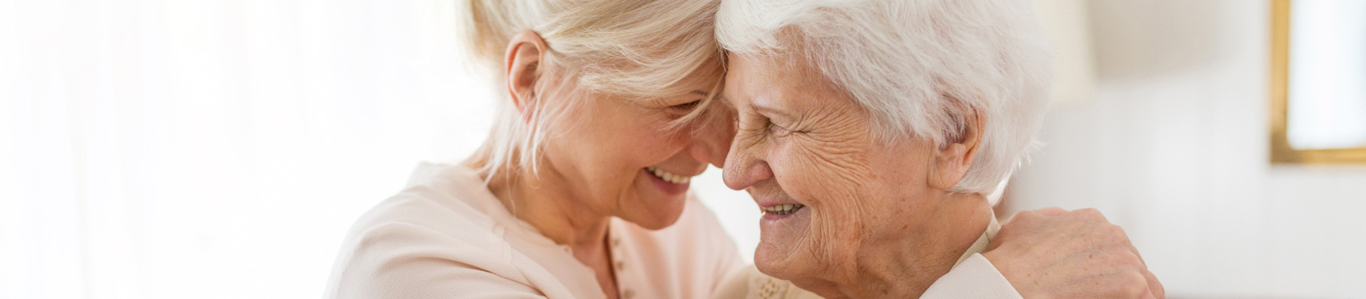 a senior woman and her adult daughter embracing one another