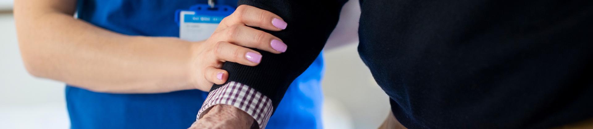 a nurse s hand on an older gentleman s arm