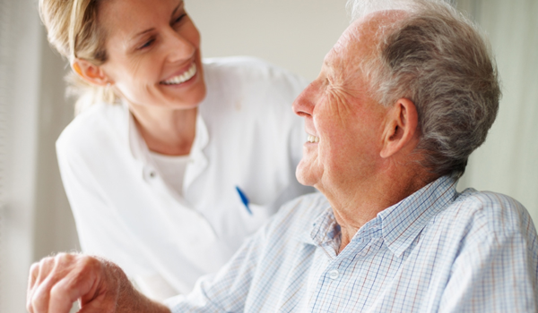 an older man talking to a nurse at his senior living community
