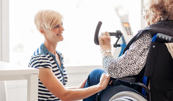 a senior woman on an exercise bike talking to a nurse