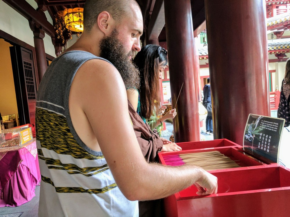 Dan lighting up some incense at the Buddha Tooth Temple in Chinatown.