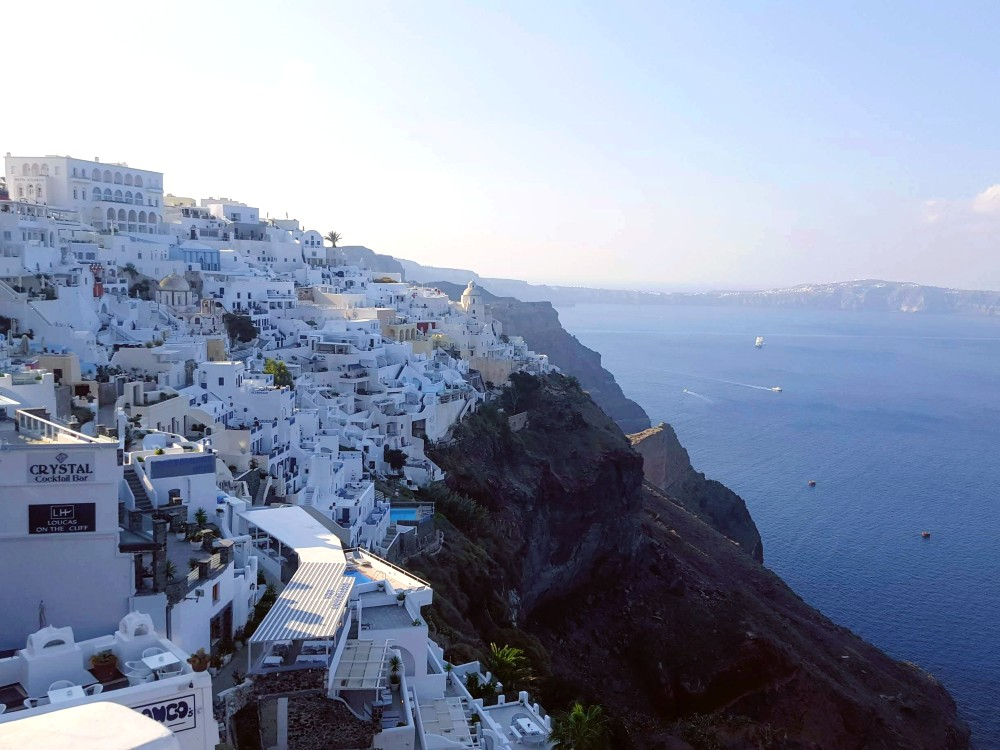 A view of buildings perched precariously atop the cliffs of Santorini.