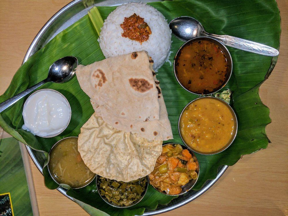A traditional-looking Indian thali, made up of rice, bread, and several different smaller dishes.