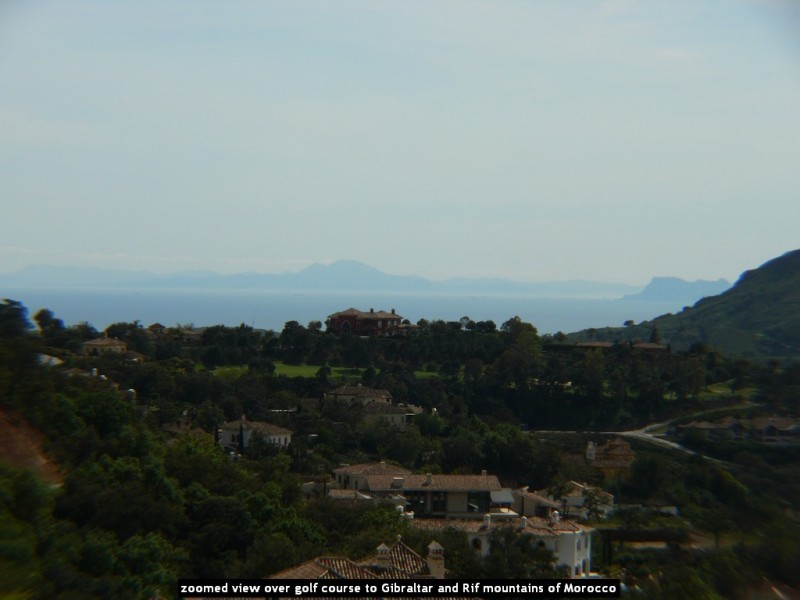 zoomed view over golf course to Gibraltar and Rif mountains of Morocco