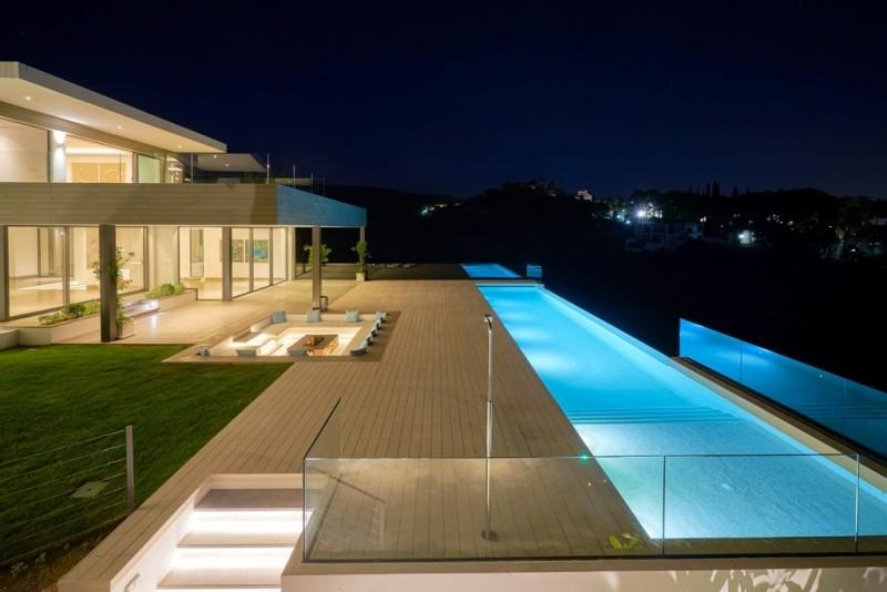 Infinity pool, garden and terrace illuminated at night