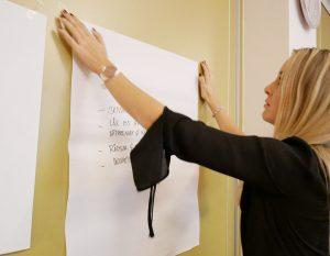 Kvinna sätter upp papper på vägg