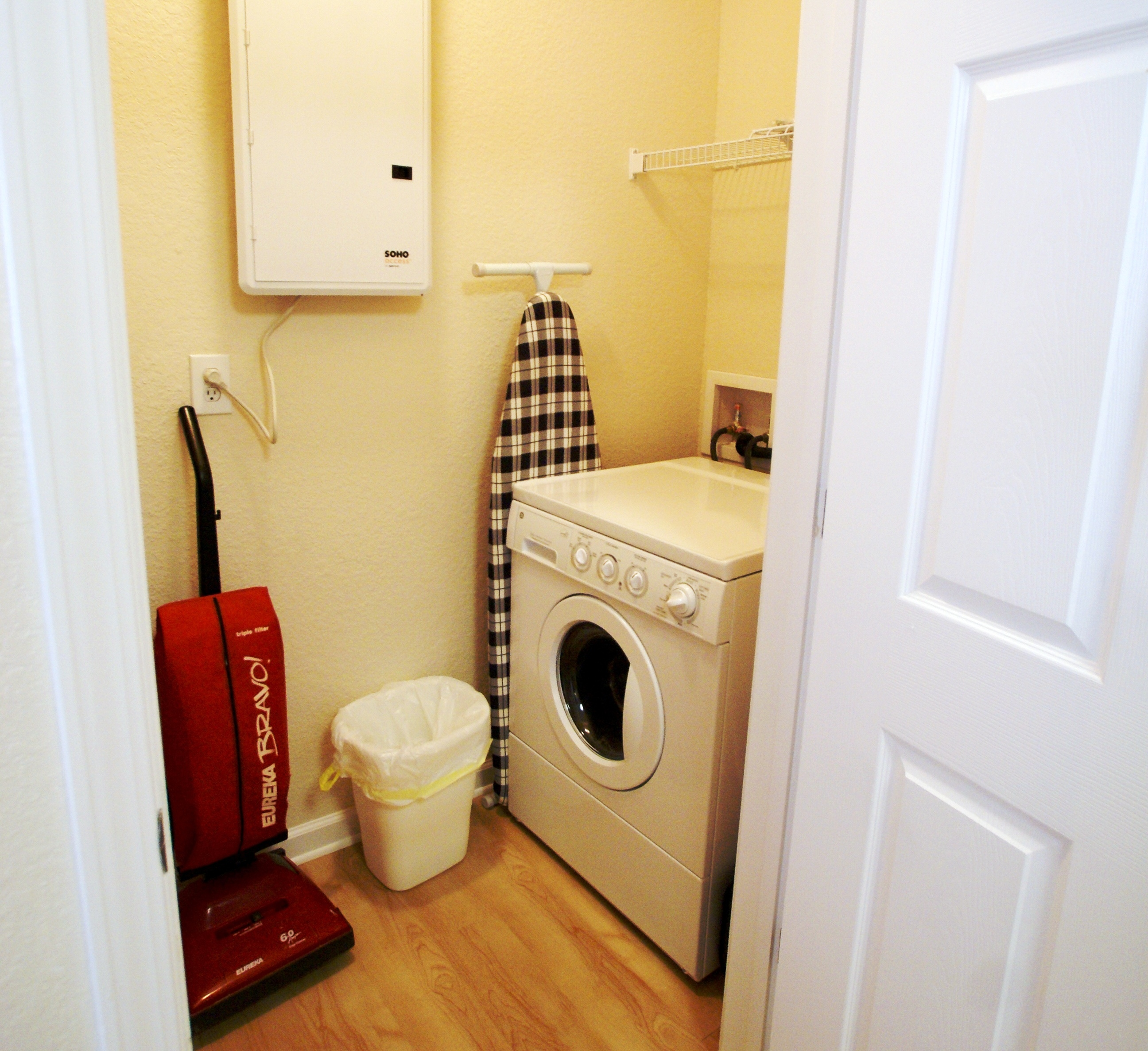 washer dryer iron ironing board vaccum laundry room shelving laundry soap trash can wood floors