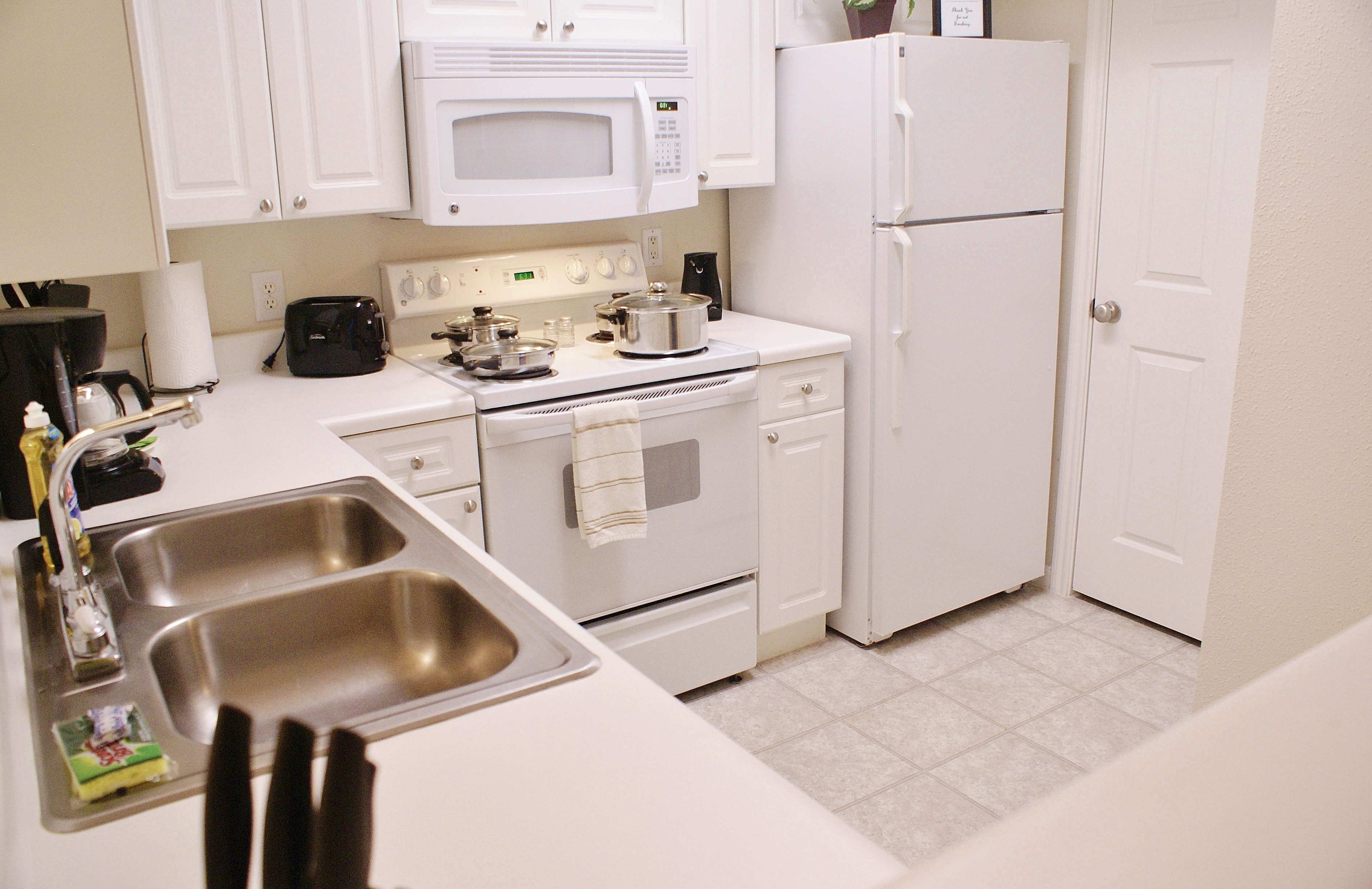 large kitchen stove oven microwave oven doube stainless steel sink coffee maker coffee mugs toaster papertowels pots and pans cookware electric can opener large kitchen towels sponge dish soap salt and peper shaker set refregerator upper and lower cabinets