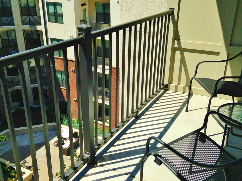 private balcony with open metal railing, two iron patio chairs facing an inner courtyard