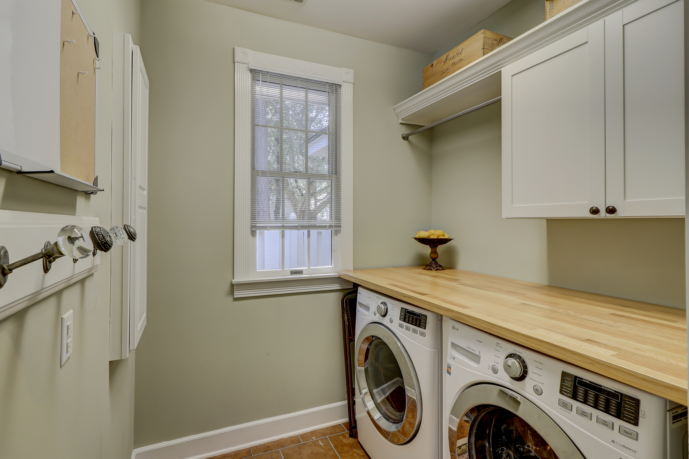 Under counter washer and dryer, butcher block counter, hanging space, wall cabinetry, natural light and built-in ironing board makes for the perfect laundry room.