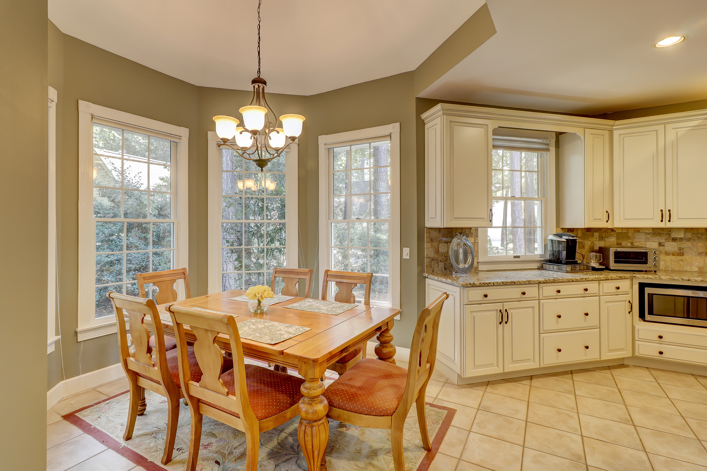 The breakfast room is tucked off to the side to allow good traffic flow and it is defined with a tray ceiling.  The breakfast room is great for casual dining and looks over the private backyard with many windows in this custom bay.