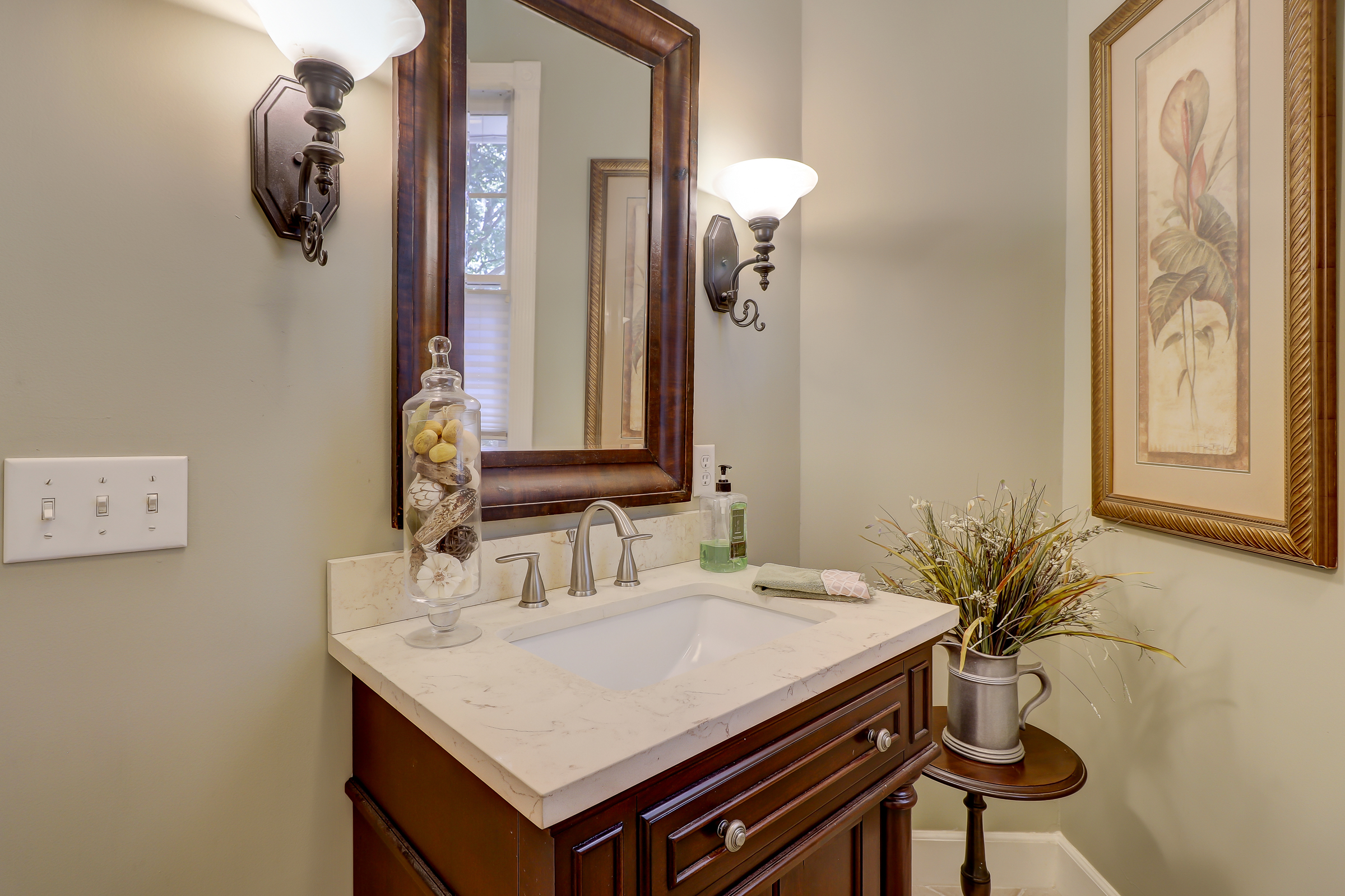 The powder room is in a private location near the kitchen.	 Tastefully finished with a furniture piece vanity, framed mirror and sconce lighting. 314 Fort Howell Dr - Palmetto Hall -  Hilton Head