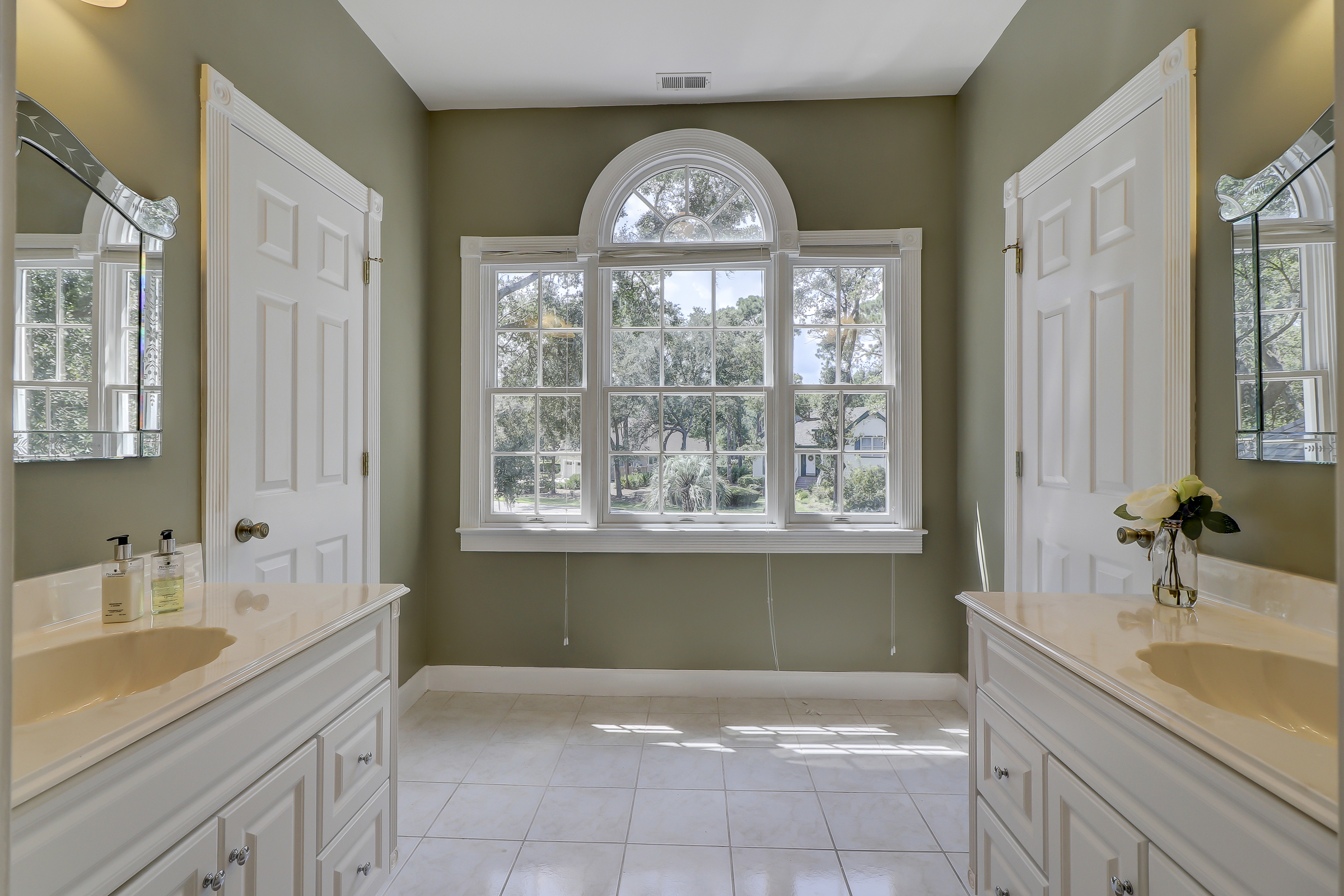 You will love this second floor Jack and Jill bath with his and her vanities and a private bath and toilet area.  Triple windows and a half round transom make this an incredibly special space.