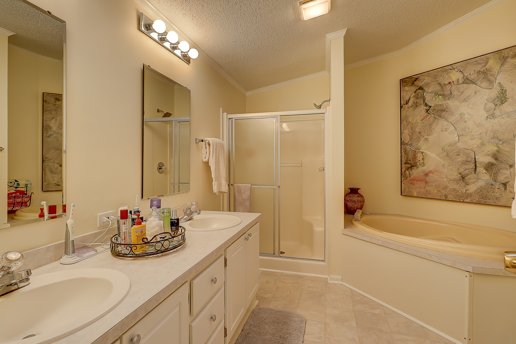 Master Bathroom with a Dressing Area, Makeup Stand, Double Vanity, Garden Tub and Separate Shower.