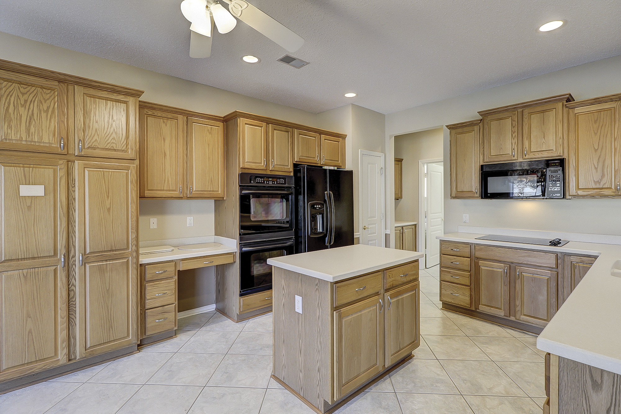 This kitchen has everything: Double ovens, cabinet pantry, pantry, desk space, island, smooth cook top, integral sink, solid surface counter tops, plenty of lighting and a ceiling fan. Sun City Hilton Head