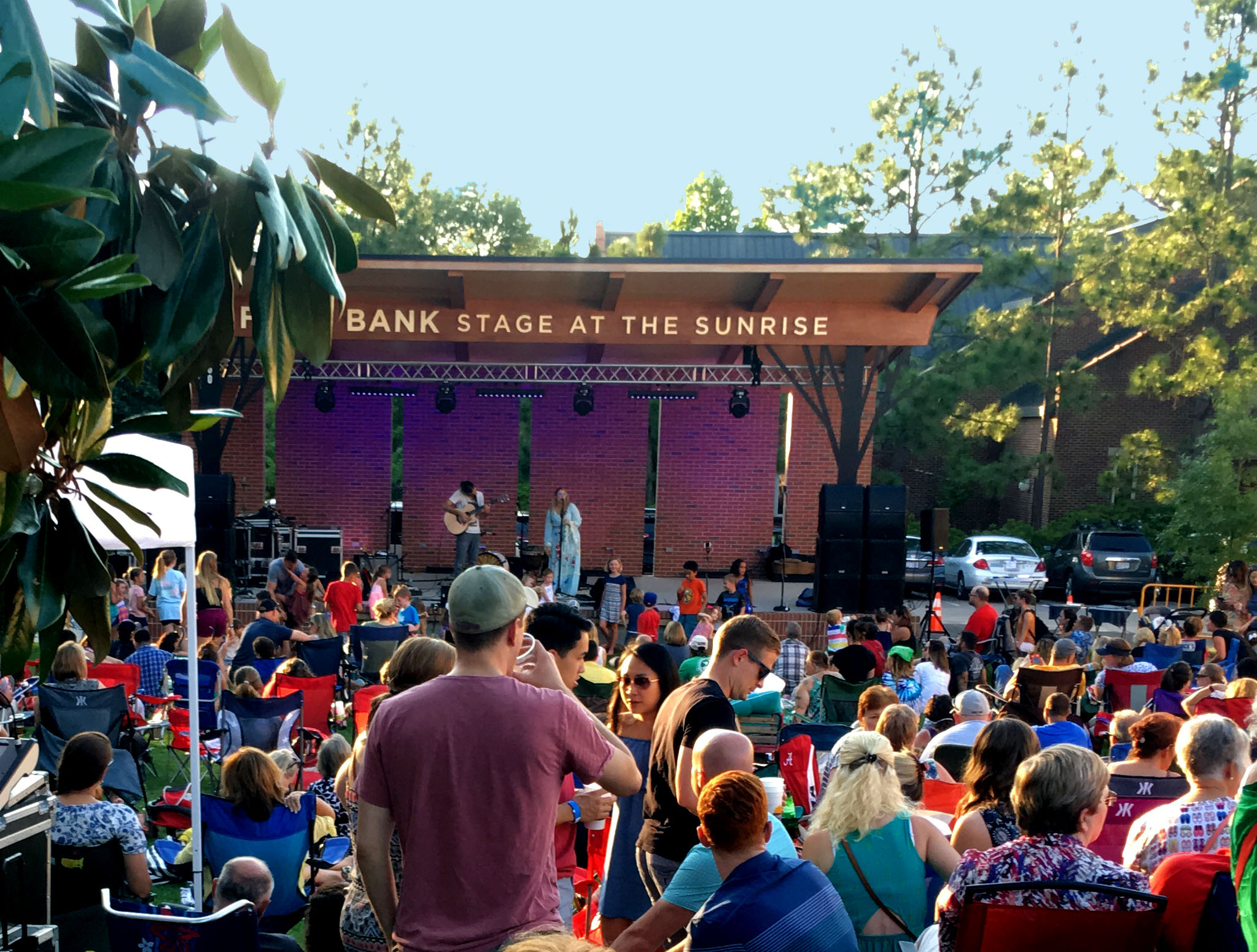 Photo of the outdoor stage at the sunrise theater with people listening to music