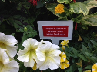 Picture of flowers with a small sign from the Moore County Master Gardeners