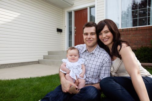 Happy Family In Front Of Their Dream Lifestyle Home