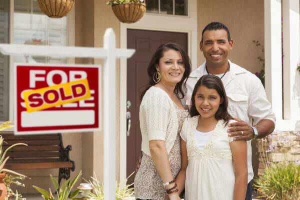 Happy Hispanic Family With Sold Sign In Front Of Home