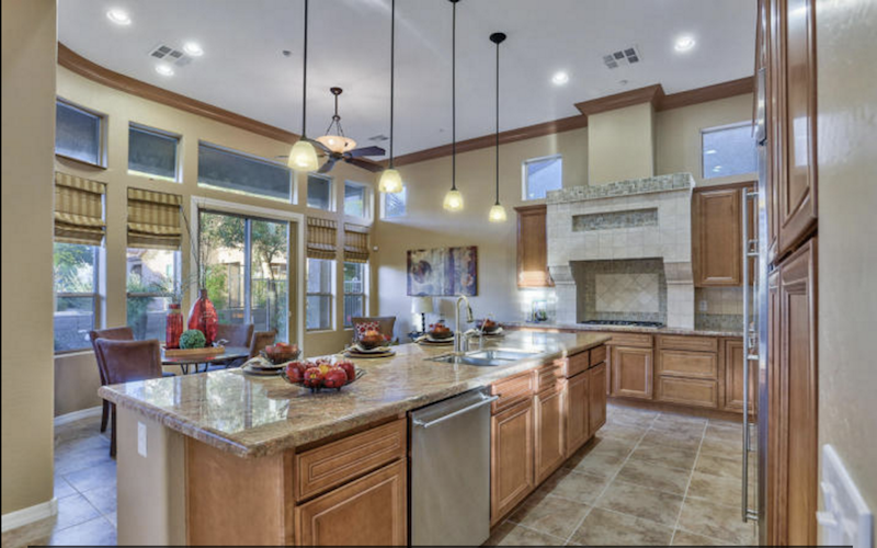 bright and spacious kitchen with stone and granite counters