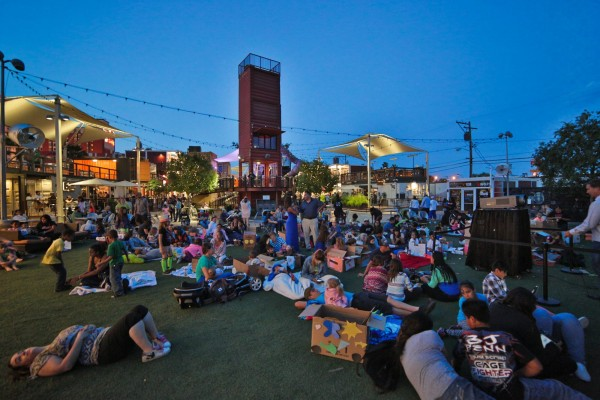 Outdoor space at Container Park featuring a grassy area, string lights, outdoor entertainment, and more.