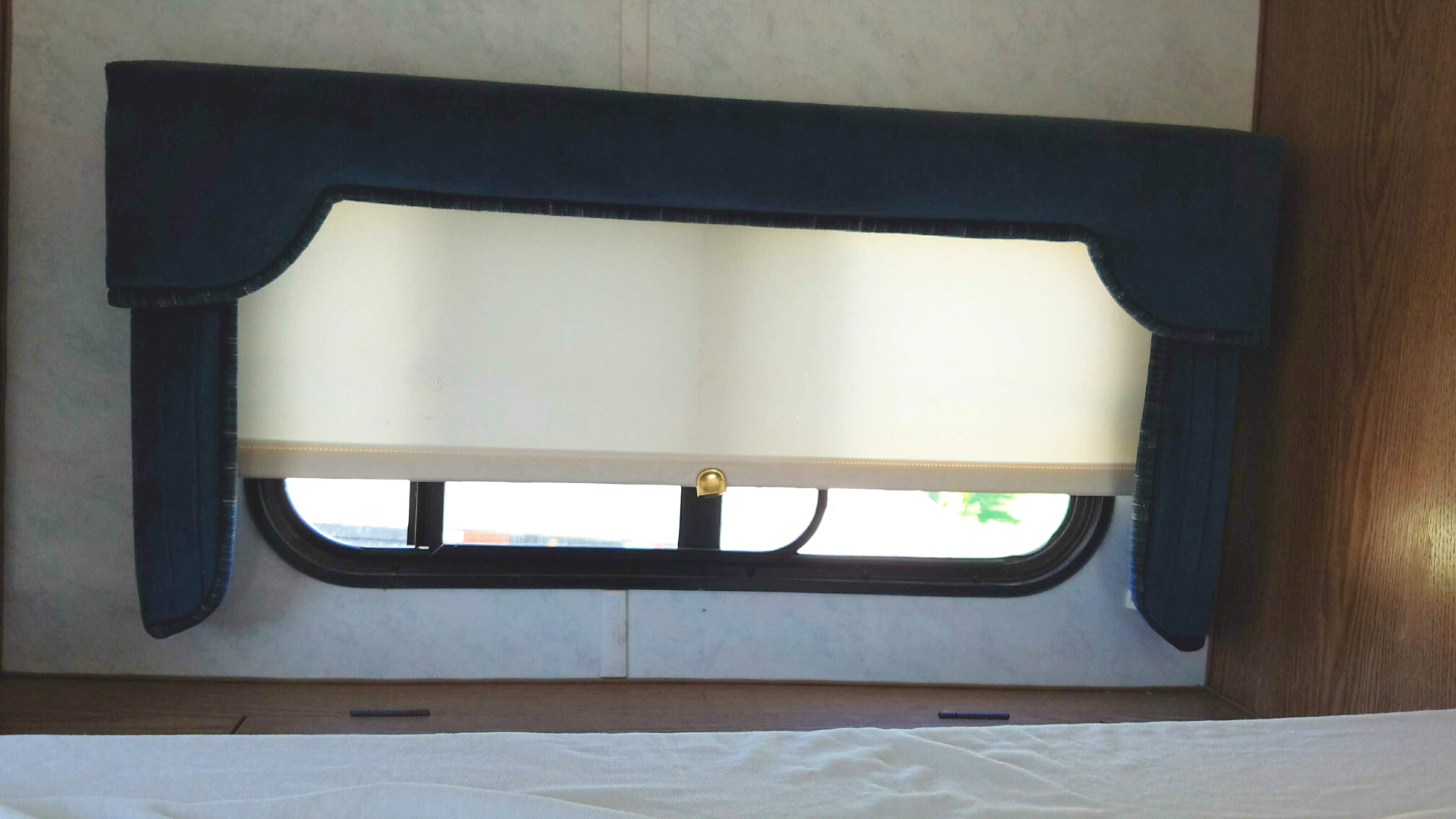 Camper window with covered cornice