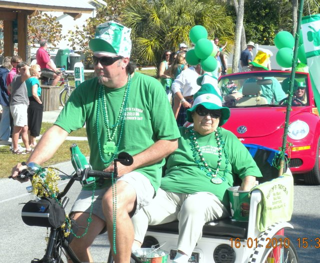 Ms. Duffy is driven in the parade by Rick Lewis in a Pedi-cab from Sarasota Pedi-cab Company