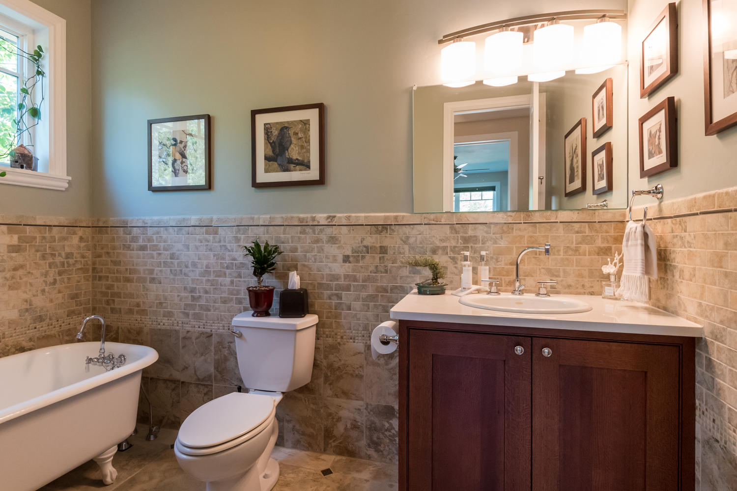 Bright, sunny bathroom with claw tub and faux brick tile