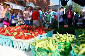 View of berries and green beans on a Farmers Market table with people in the background
