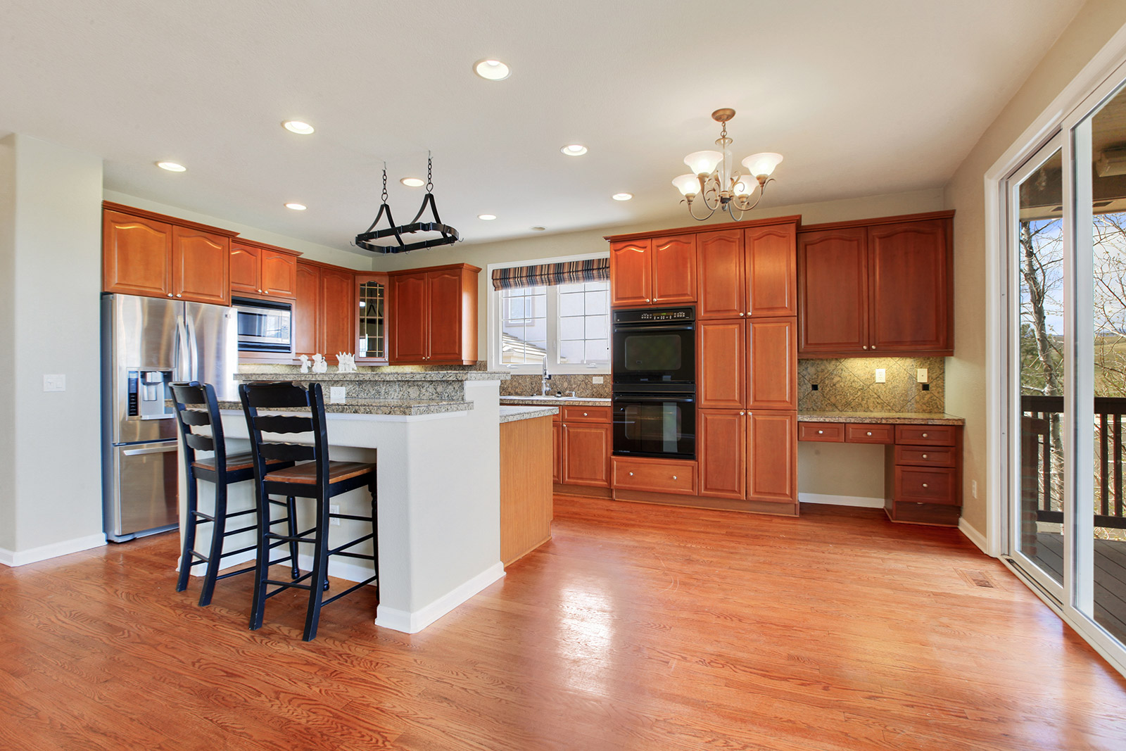 View of new, bright, modern kitchen with barstools at island