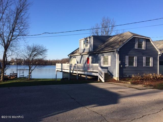 Image is an exterior shot of the below described waterfront home for sale on Round Lake, one of the Sister Lakes, in Dowagiac, Michigan.