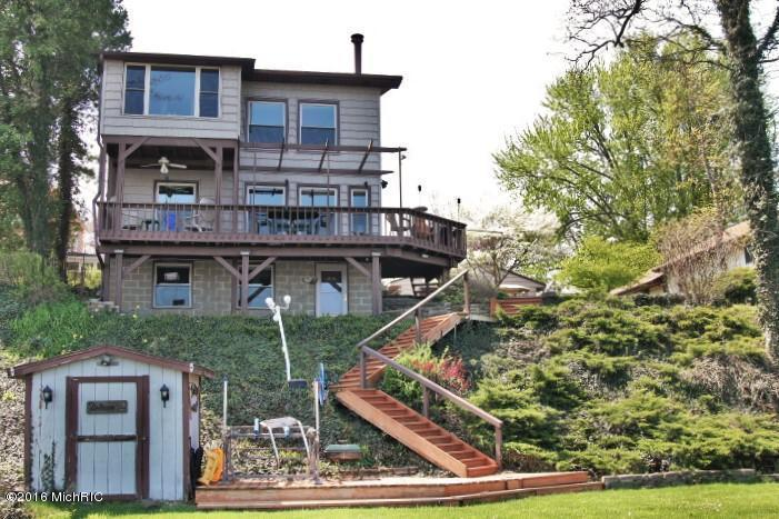Image is an exterior shot of the described home for sale on Paw Paw Lake in Coloma, Michigan.