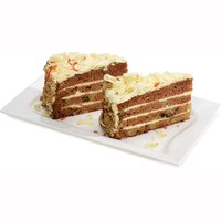 Two Sliced Pieces of Moist and Rich Pineapple Walnut Carrot Cake is Smothered with a Rich and Creamy Cream Cheese Icing and Surrounded by Walnuts and Topped with Delicate White Chocolate Curls. Each Slice - Approx 150g
