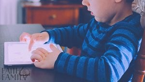 Child sitting at table using ipad