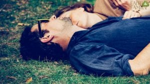 Husband and wife laying on the grass and relaxing