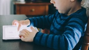 Child sitting at table using ipad