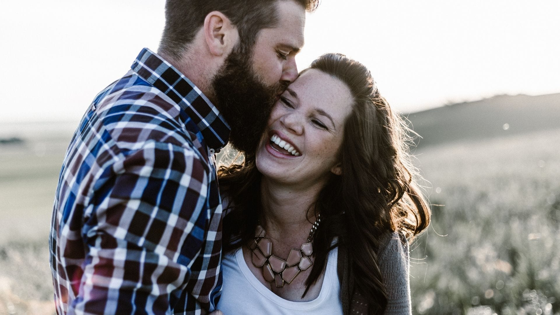 Husband holding wife close and kissing her forehead.