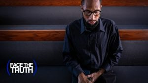 man sitting on a pew praying