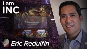 Man smiling and a arena with a big screen filled with people with text overlay I am INC, Eric Redulfin