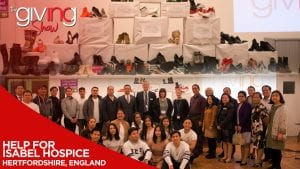 INCGiving volunteers and Isabel Hospice employees with display of shoes donated by volunteers with overlay text Help for Isabel Hospice. Hertfordshire England