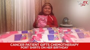Cancer patient posing with shirts with pink bow made for fundraiser.