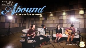 "Group of singers in studio sitting on couches with text overlay: ""Abound Live Studio Session"""