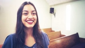 Young woman smiling at camera with pews behind her.