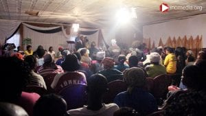minister in south africa preaching to a crowded room