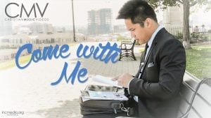 """Man sitting on park bench looking at a piece of paper with text overlay: """"Come with me"""""""