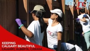 Volunteers painting wooden gate with overlay text Keeping Calgary Beautiful